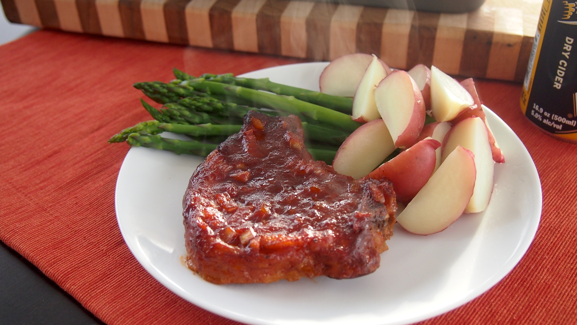 Barbecue pork chops served with asparagus and red new potatoes.