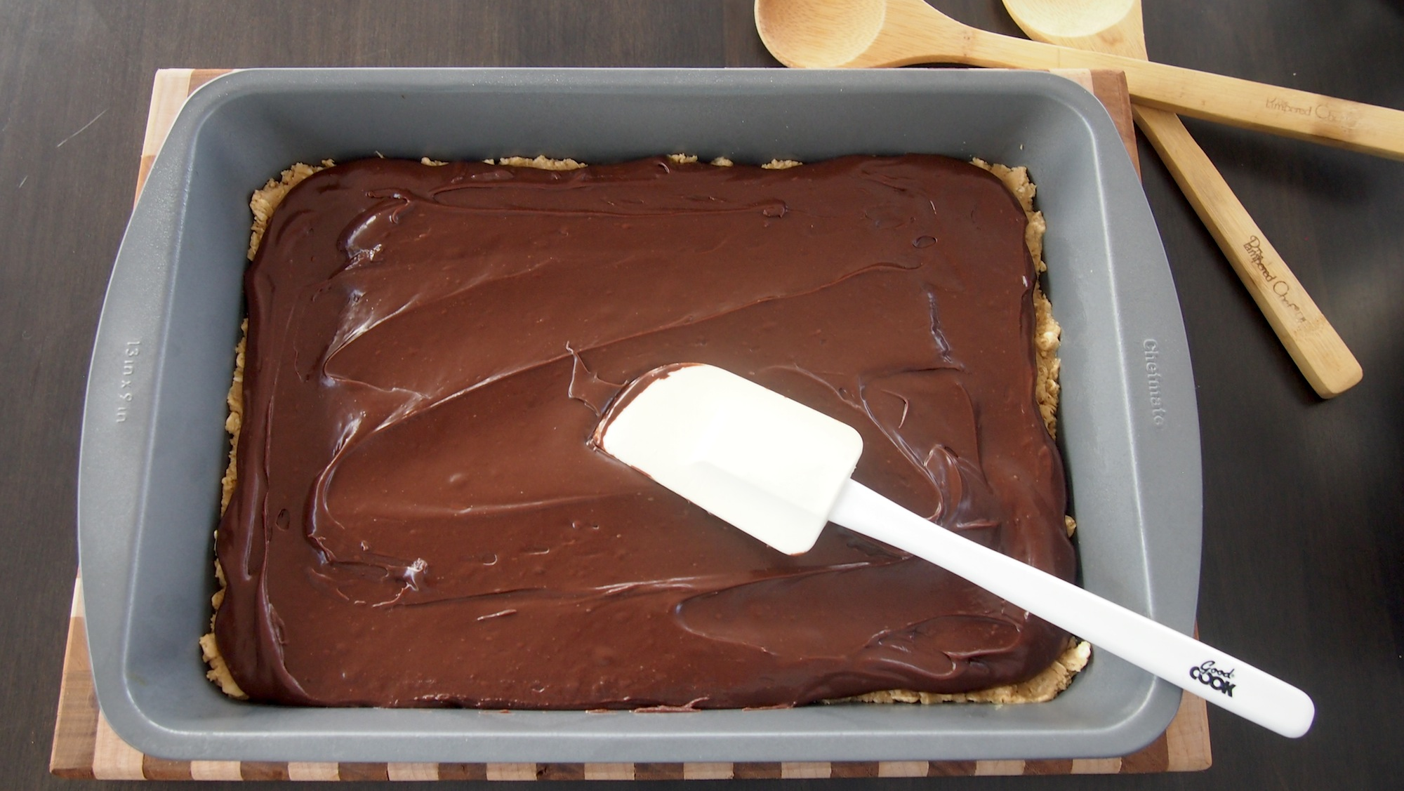 The chocolate mixture is spread on top of a layer of the oatmeal mixture pressed into the pan.