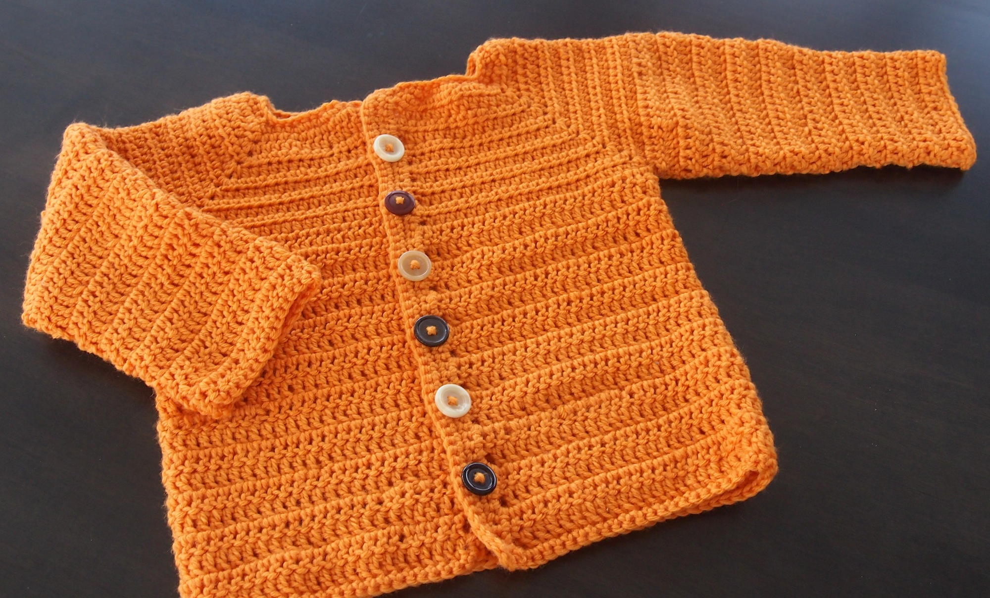 Orange crocheted sweater with white, black, and red buttons.